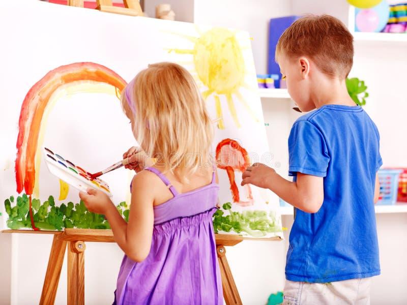 Het schilderen van het kind bij schildersezel. stock afbeeldingen