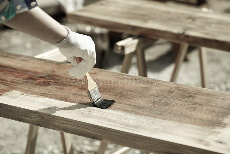 Het schilderen van hout met houten beschermingsverf royalty-vrije stock afbeelding