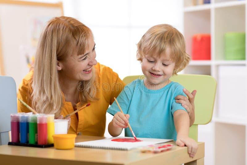 Het schilderen van het kind in kleuterschool Leraarshulp door weinig jongen stock afbeelding