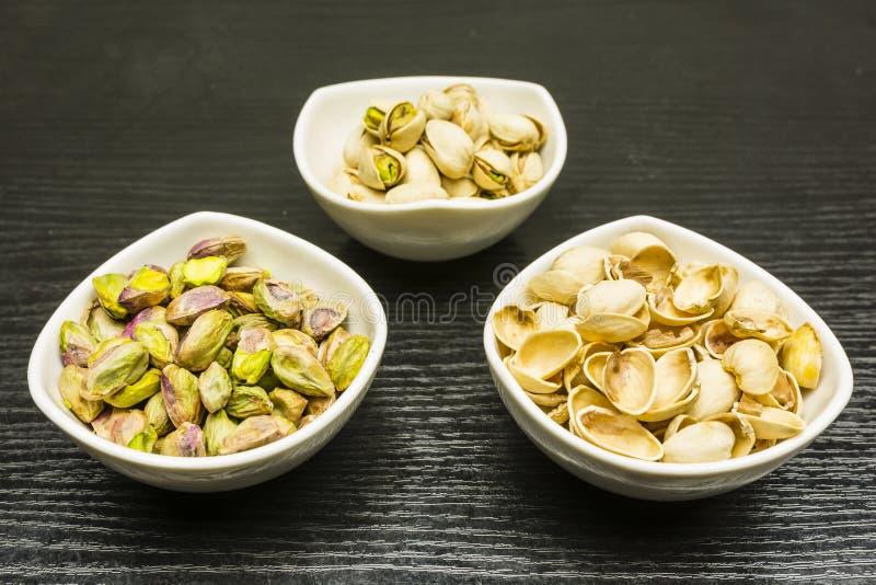Het schillen van pistachenoten Geheel, notedop en gepelde pistaches in kommen stock afbeeldingen