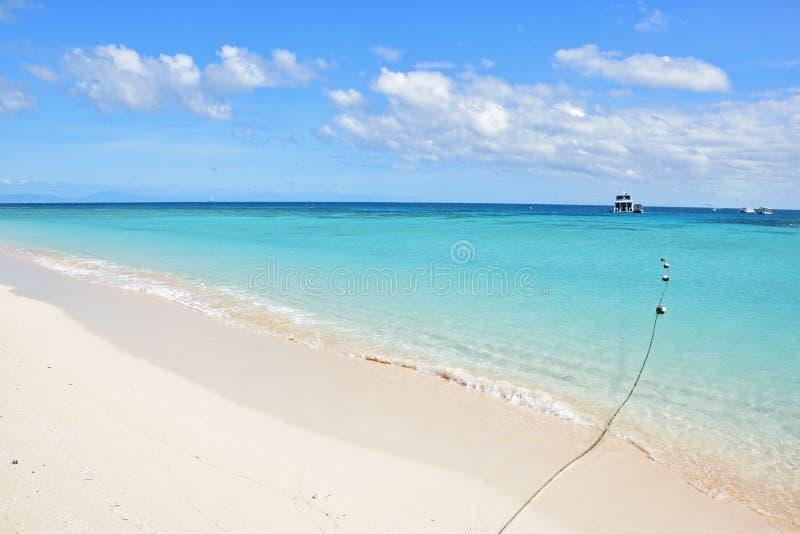 Het schip die van de dagtochttoerist bij michaelmascay dokken met mooi fijn wit zand en turkoois blauw water stock foto