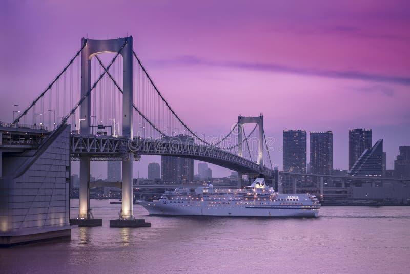 Het schip die van de Venuscruise in Odaiba-Baai onder de Regenboogbrug varen stock afbeelding