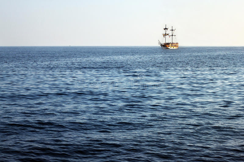 Het schip van de toeristenpiraat op de horizon stock afbeelding