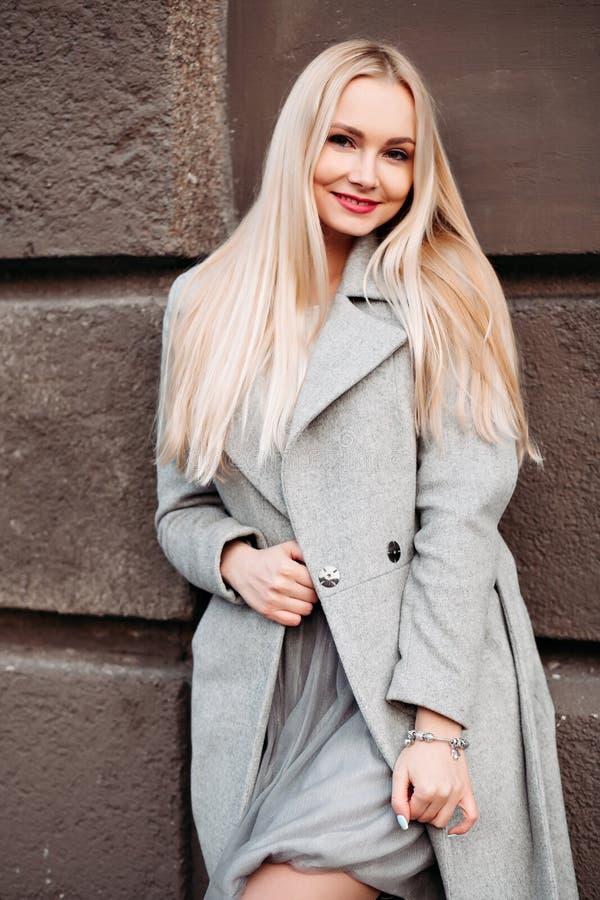 Het schitterende blonde stellen bij straat in grijze laag stock afbeeldingen