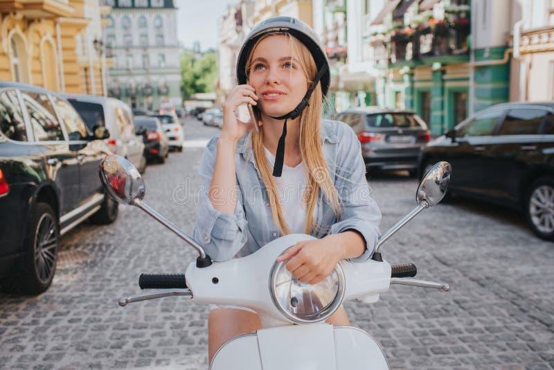 Het schitterende blondemeisje in helm stelt op camera Zij glimlacht Het meisje zit op motorfiets in het midden van stock fotografie