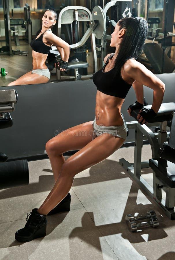 Het schitterende donkerbruine werken aan haar buik in een gymnastiek, spiegelbezinning Geschiktheidsvrouw die training doen Sport stock afbeeldingen
