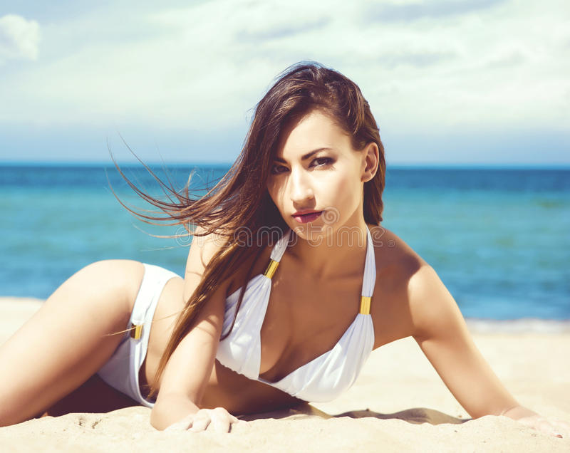 Het schitterende en mooie jonge meisje ontspannen op een de zomerstrand royalty-vrije stock afbeelding