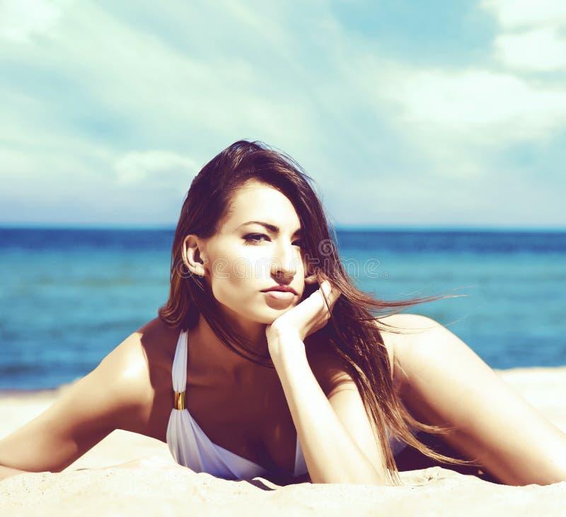 Het schitterende en mooie jonge meisje ontspannen op een de zomerstrand stock foto