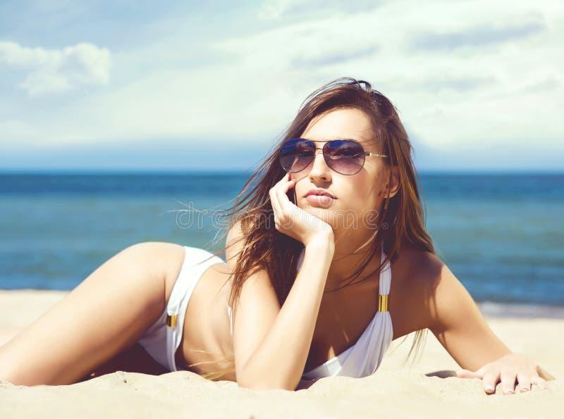 Het schitterende en mooie jonge meisje ontspannen op een de zomerstrand royalty-vrije stock fotografie