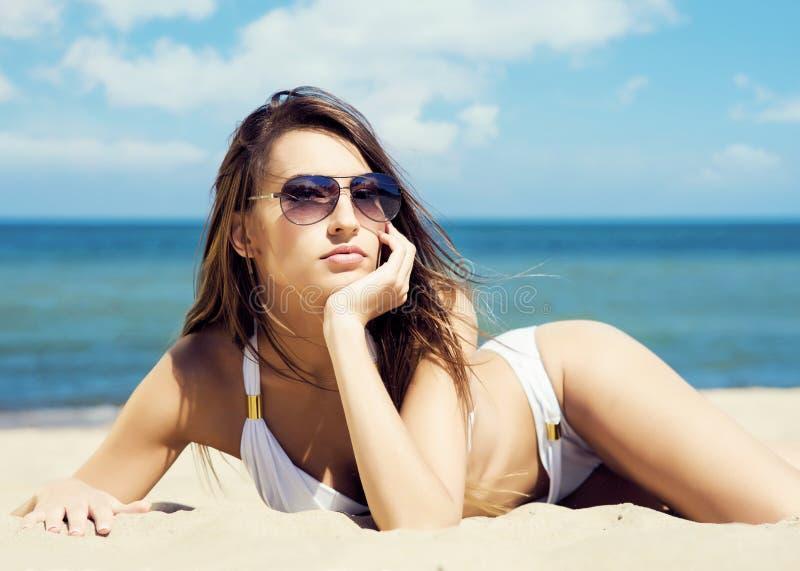 Het schitterende en mooie jonge meisje ontspannen op een de zomerstrand stock afbeeldingen