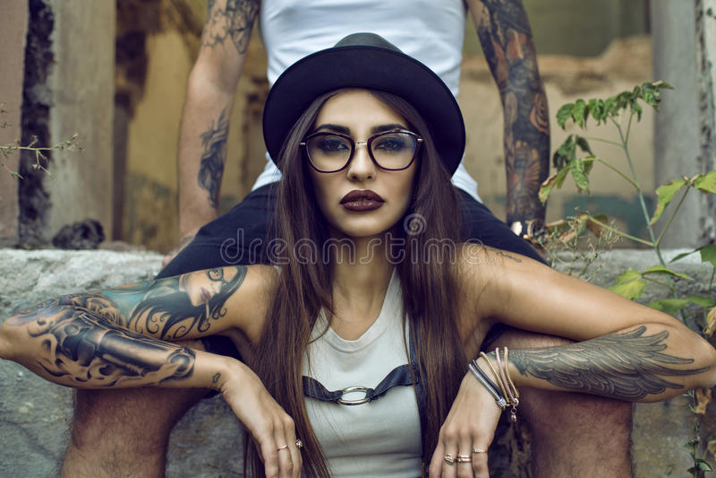 Het schitterende getatoeeerde meisje met provocatief maakt omhoog het zitten tussen haar boyfriend& x27; s benen in het geruïneer stock foto's
