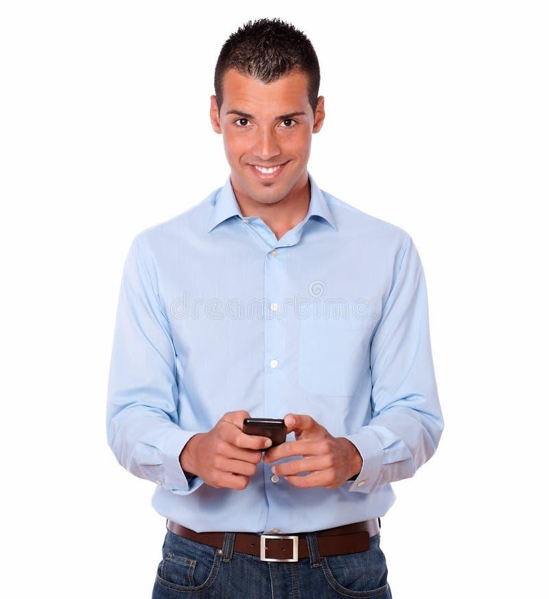 Het schitterende jonge mens texting met zijn cellphone stock afbeelding