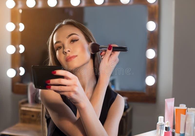 Het schitterende meisje zet op make-up royalty-vrije stock afbeelding