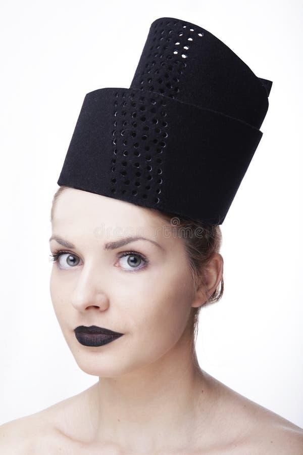 Het schitterende model van de blondevrouw met blauwe ogen en zwarte lippenstift die het grote hoofddeksel van de modieuze ontwerp stock fotografie