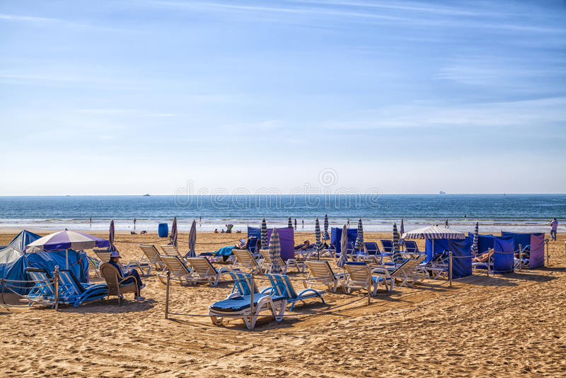 Het schitterende strand dichtbij Agadir in Marokko met lichtgevende blauwe hemel en blauwe ligstoelen stock afbeelding