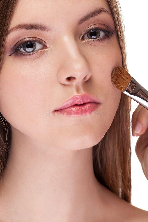 Het schitterende vrouw van toepassing zijn maakt omhoog op haar gezicht met een borstel stock fotografie