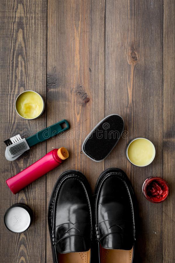 Het schoenpoetsmiddel, borstels, zet dichtbij zwarte glanzende leerschoenen in de was op de donkere houten ruimte van het achterg royalty-vrije stock fotografie
