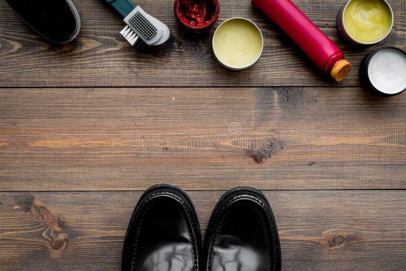 Het schoenpoetsmiddel, borstels, zet dichtbij zwarte glanzende leerschoenen in de was op de donkere houten ruimte van het achterg royalty-vrije stock afbeelding