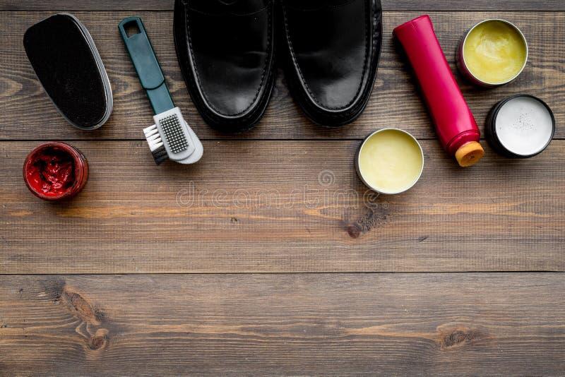 Het schoenpoetsmiddel, borstels, zet dichtbij zwarte glanzende leerschoenen in de was op de donkere houten ruimte van het achterg stock foto