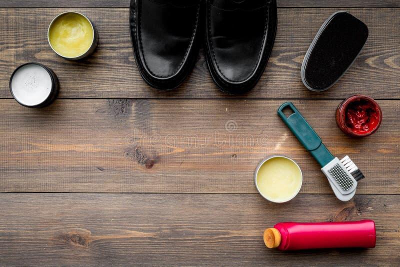 Het schoenpoetsmiddel, borstels, zet dichtbij zwarte glanzende leerschoenen in de was op de donkere houten ruimte van het achterg stock afbeelding
