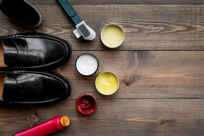 Het schoenpoetsmiddel, borstels, zet dichtbij zwarte glanzende leerschoenen in de was op de donkere houten ruimte van het achterg royalty-vrije stock foto