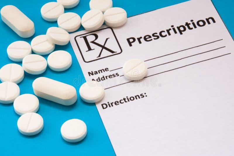 Het schone recept voor de verklaring van de voorschriftdrug is dichtbij verspreide witte pillen en tabletten op een blauwe achter royalty-vrije stock foto's