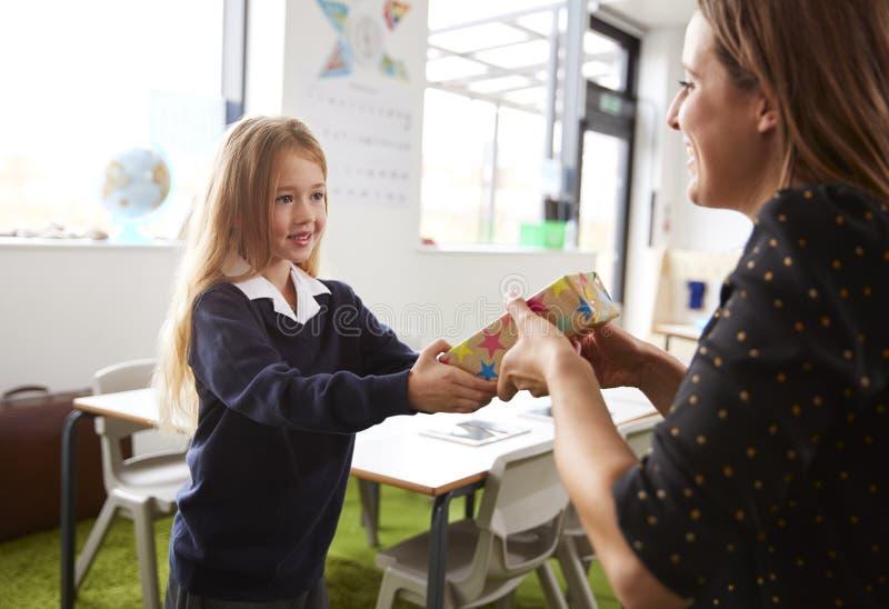 Het schoolmeisje bij een lage school die een gift voorstellen aan haar vrouwelijke leraar in een klaslokaal, sluit omhoog royalty-vrije stock afbeelding