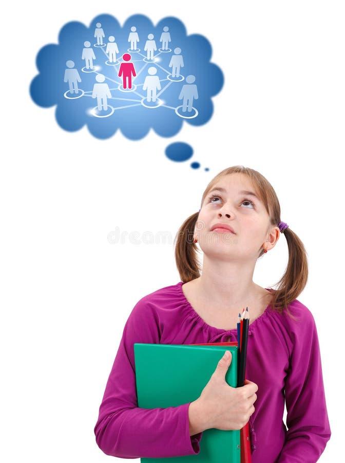 Het schoolmeisje dat van de tiener over sociaal netwerk denkt stock afbeelding