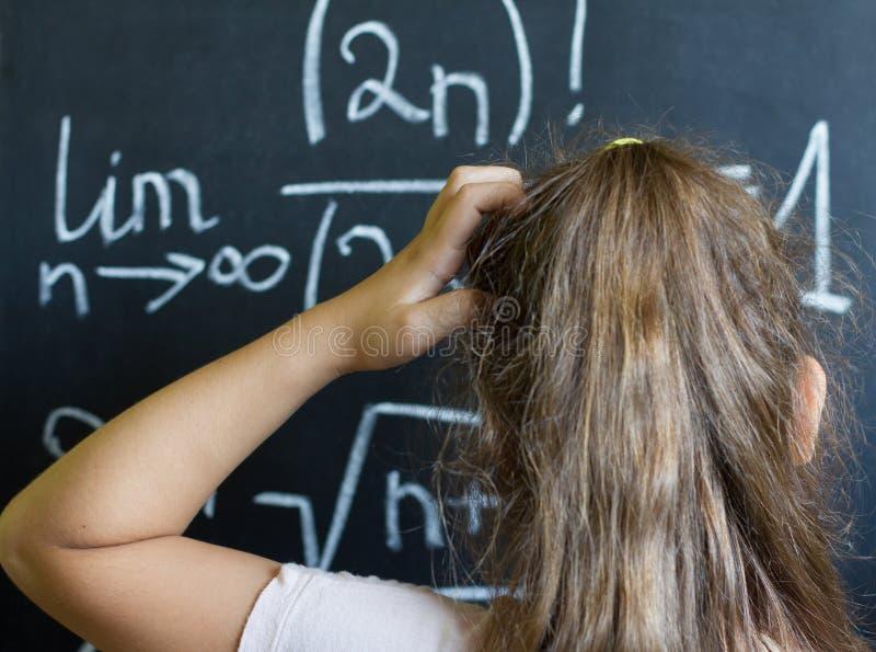 Het schoolmeisje denkt op de moeilijke taak van wiskunde stock fotografie