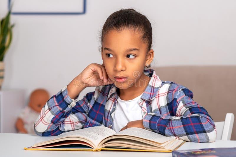 Het schoolmeisje die bij de lijst situeren binnen en zijn thuiswerk doen stock afbeelding