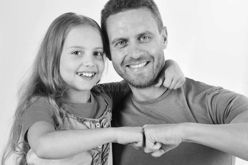 Het schoolmeisje en de papa slaan vuisten in overeenkomst Kinderjaren en familie royalty-vrije stock foto