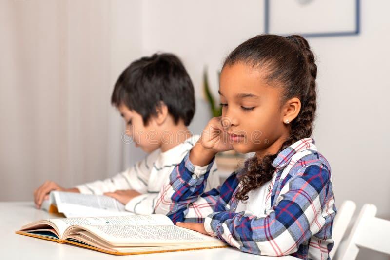Het schoolmeisje en schooljongen die bij de lijst situeren binnen en hun thuiswerk de doen stock afbeeldingen