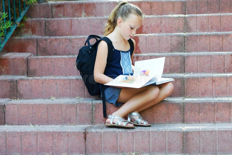Het schoolmeisje 8 jaar oud het doen thuiswerk op treden leest boek royalty-vrije stock afbeelding