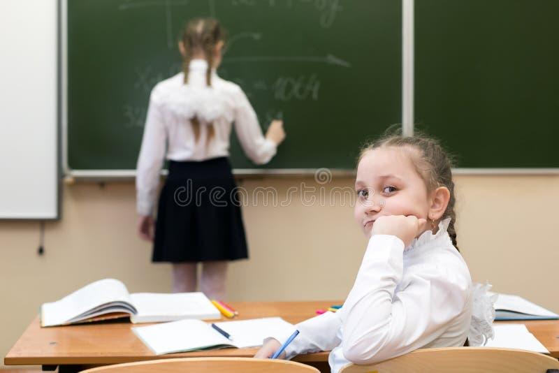 Het schoolmeisje kijkt terug terwijl een vriend bij het bord schrijft stock afbeelding