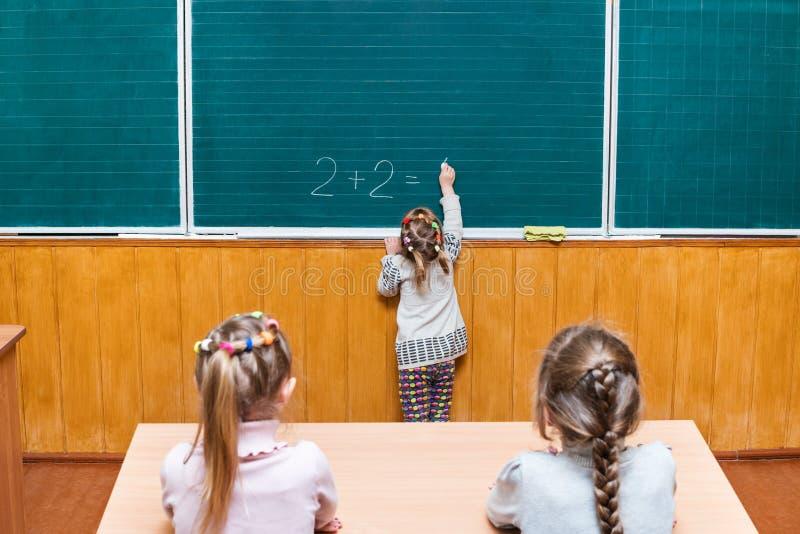 Het schoolmeisje lost een voorbeeld van wiskunde op stock foto
