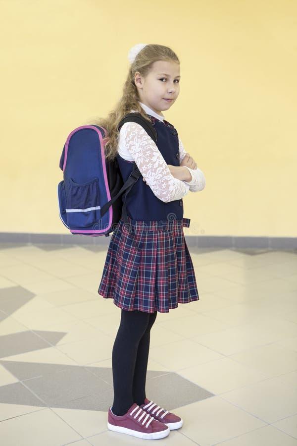 Het schoolmeisje van de Firdklasse met rugzak die zich in schoolzaal bevinden, volledig lengteportret royalty-vrije stock foto's