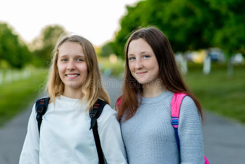Het schoolmeisje van twee meisjesvrienden De meisjes rusten na school De zomer in aard Achter rugzakken Het beste concept vriends royalty-vrije stock afbeelding