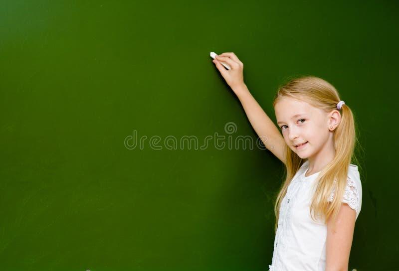Het schoolmeisje wil iets op het bord schrijven stock fotografie