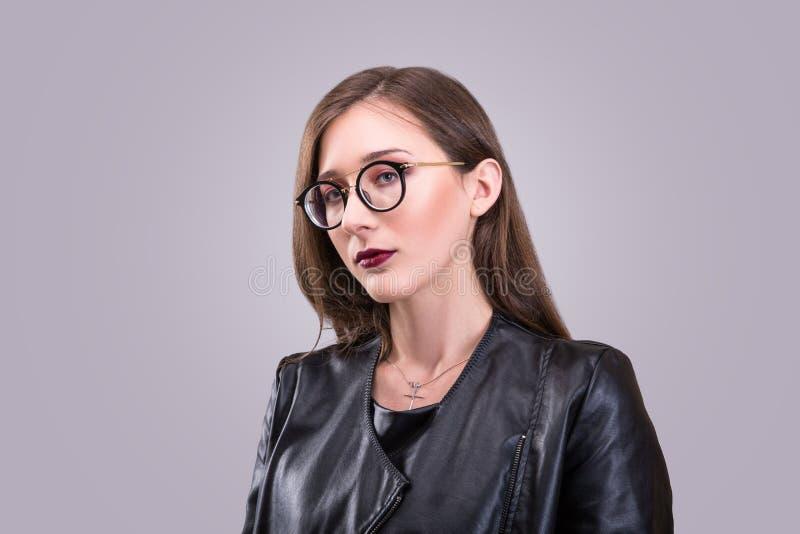Het schoonheidsportret van jonge aantrekkelijke vrouw die glazen met agressieve samenstelling dragen kleedde zich in laitherjasje royalty-vrije stock foto