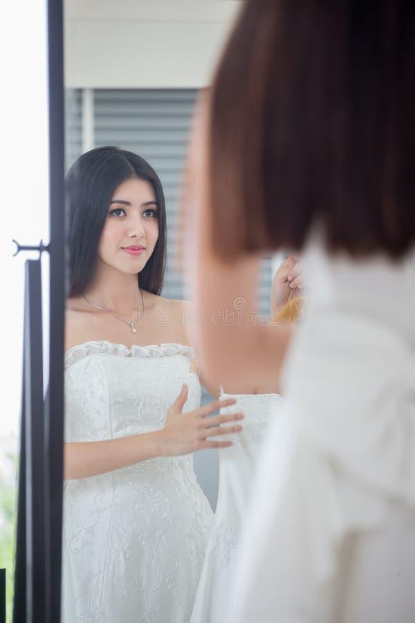 Het schoonheidsportret van jonge Aziatische bruid onderzoekt de spiegel en glimlacht terwijl het kiezen van huwelijkskleding in h stock afbeeldingen