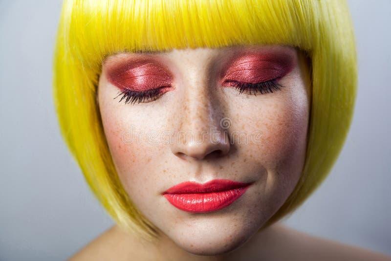 Het schoonheidsportret van kalm leuk jong vrouwelijk model met sproeten, rode make-up en gele pruik, sloot ogen met ontspannen er stock afbeelding