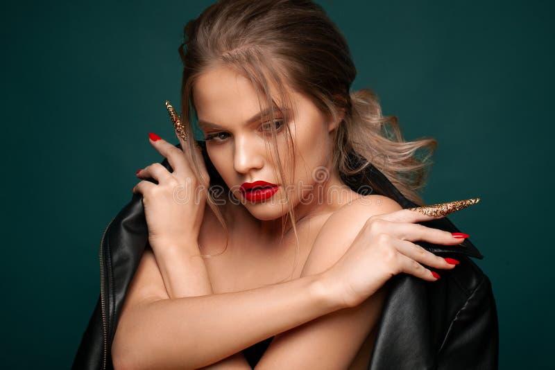 Het schoonheidsportret van vrij sexy vrouw met rode lippen, rode en gouden spijkers, nagelt decoratie, juwelen royalty-vrije stock afbeelding