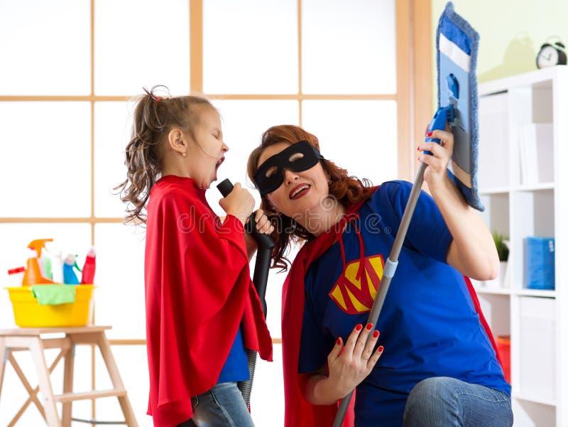 Het schoonmaken concept Super van de heldenvrouw en dochter het spelen gitaar en het zingen bij het schoonmaken van materiaal Fam stock afbeeldingen