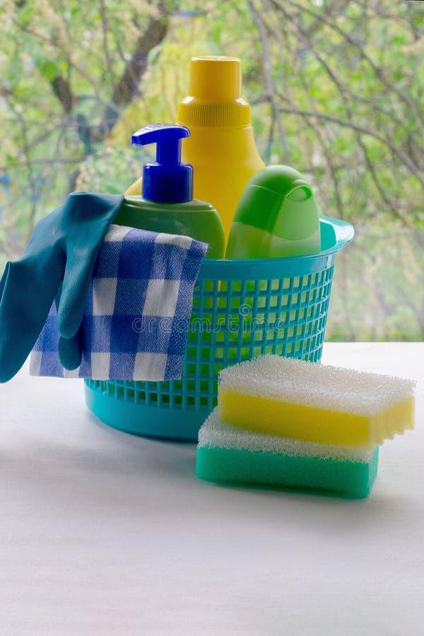 Het schoonmaken Mand met sponsen en flessen van chemische producten Rubberhandschoenen en keukenrol Huishoudenchemische producten stock afbeeldingen