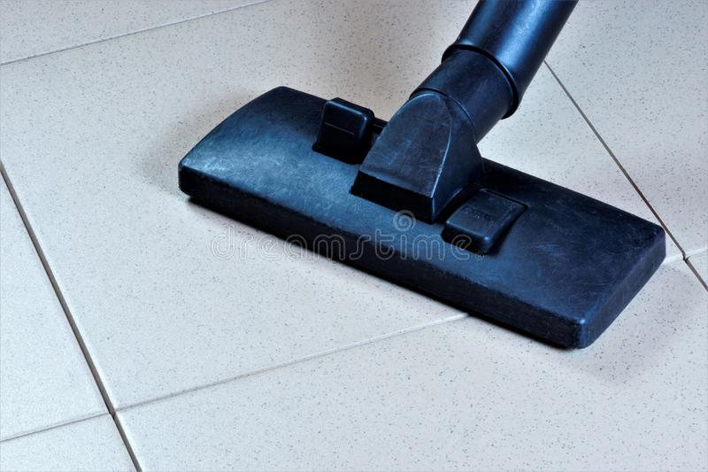Het schoonmaken van de betegelde vloeroppervlakte met een stofzuiger, sanitaire restauratie van netheid van puin Handhaaf veilige royalty-vrije stock afbeeldingen