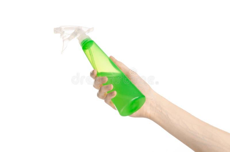 Het schoonmaken van het huis en het schonere thema: man hand die een groene nevelfles voor schoonmaken houden geïsoleerd op een w stock foto