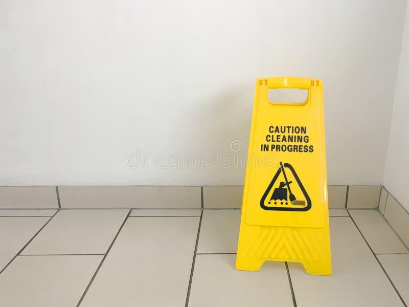 Het schoonmaken van lopend voorzichtigheids geel teken op bureauvloer stock foto