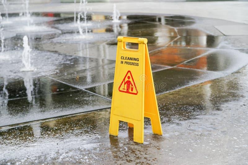 Het schoonmaken van lopend waarschuwingsbord dichtbij nat gebied stock fotografie