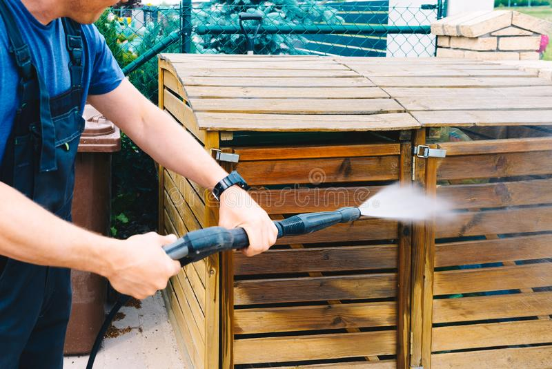 Het schoonmaken van vuil houten tuinhuisvuil met een hoge druk cleane royalty-vrije stock afbeelding