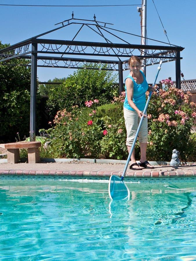 Het schoonmakende zwembad van de vrouw stock afbeeldingen